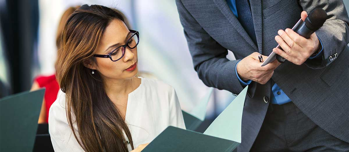 A young Asian business woman showing a document to business man in meeting.