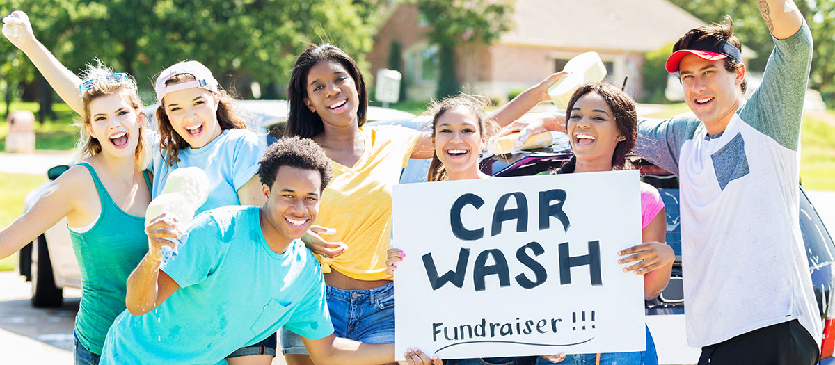 Teenagers holding sign for car wash fundraiser