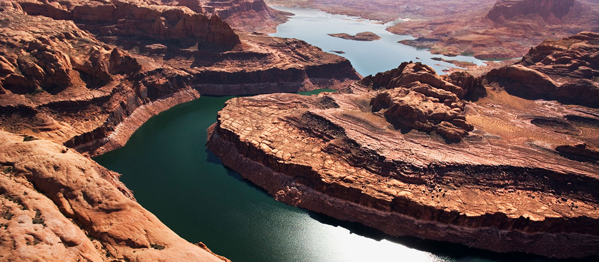 An aerial shot of the Colorado River winding through red cliffs