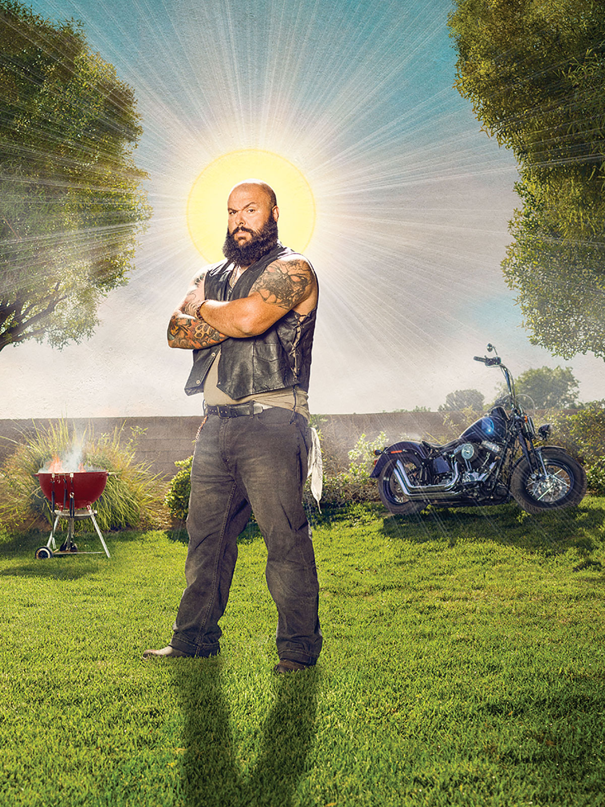 A biker stands in his lawn with a barbecue and his motorcyle in the background.