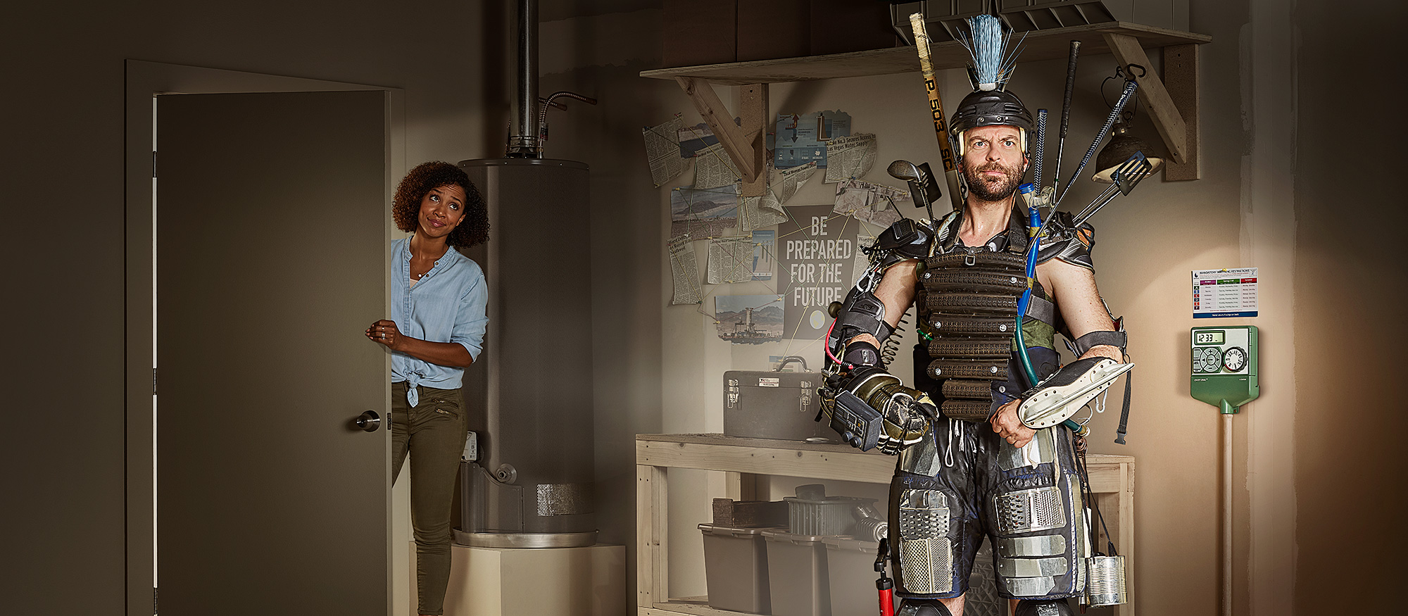 A man stands in his garage in a Mad Max style costume prepared for the future while he wife looks in on him