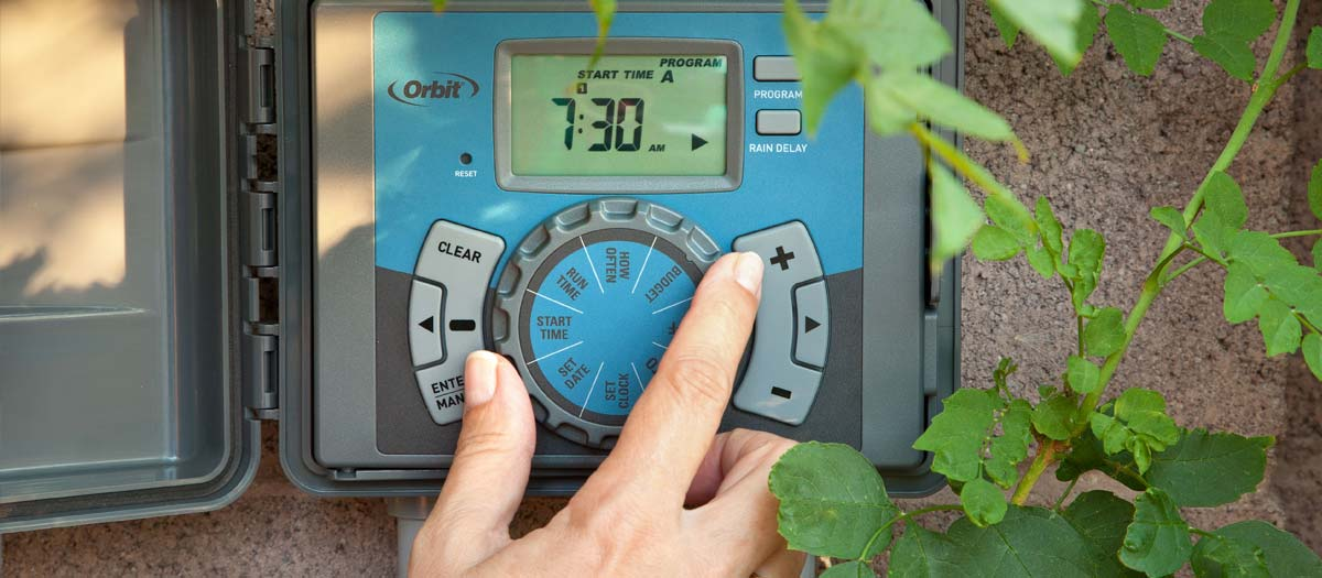 Close up of hand adjusting a irrigation clock
