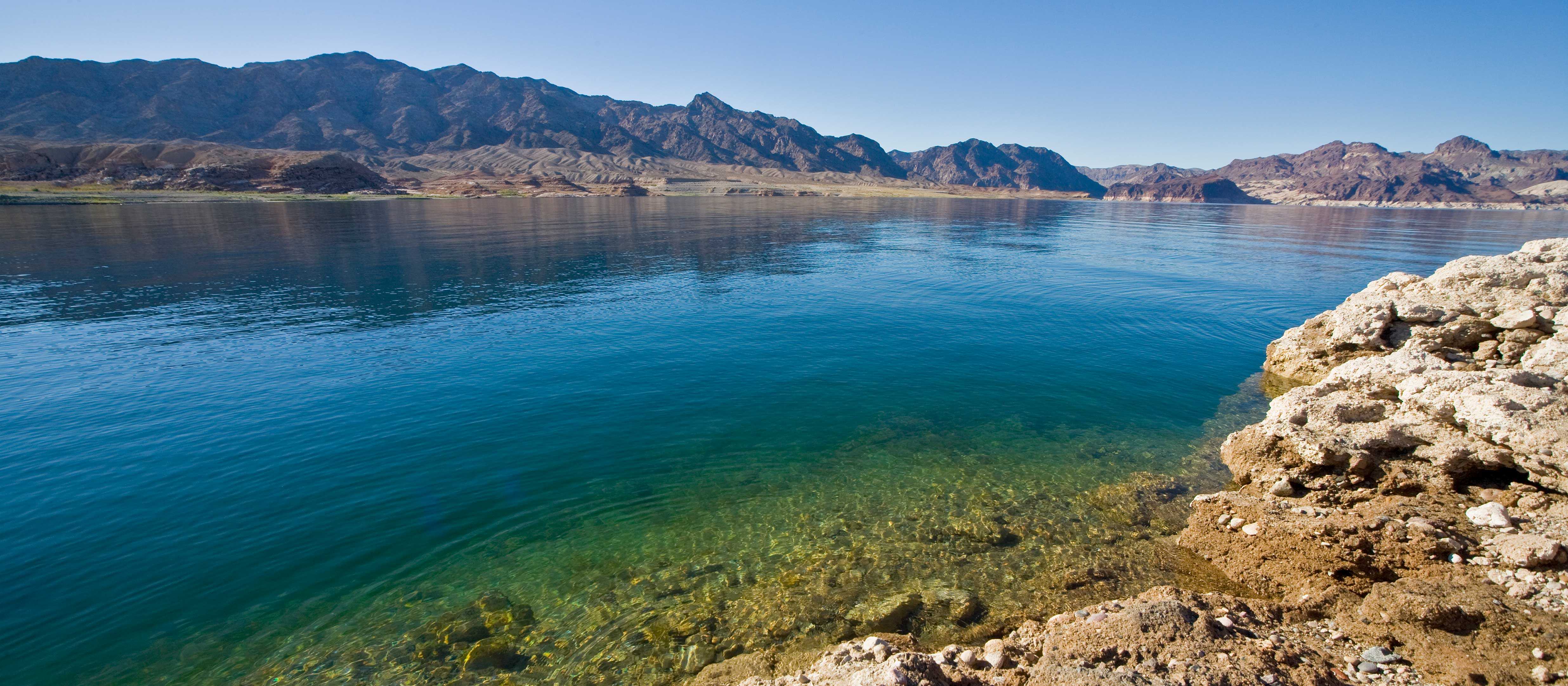 Blue-green waters of Lake Mead with mountains in the background.