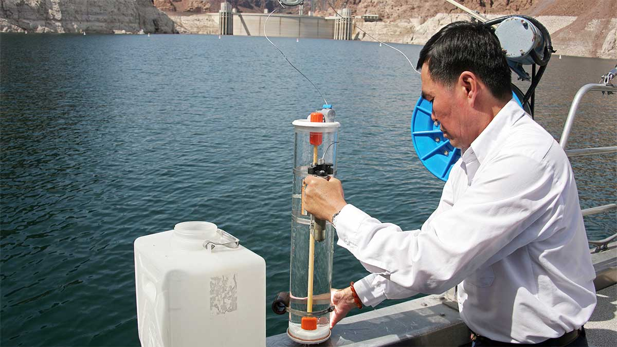 employee conducting water sampling from side of boat at Lake Mead