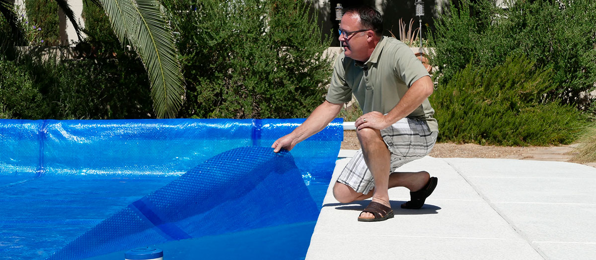 Man pulling cover on pool