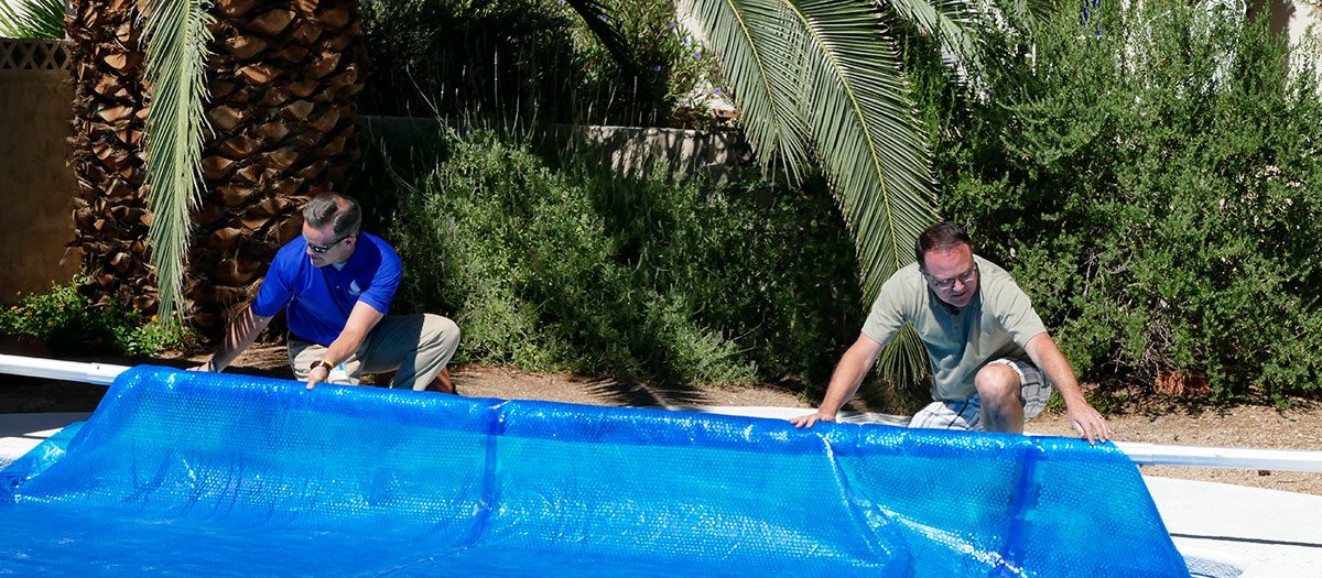 Men pulling blue pool cover over pool
