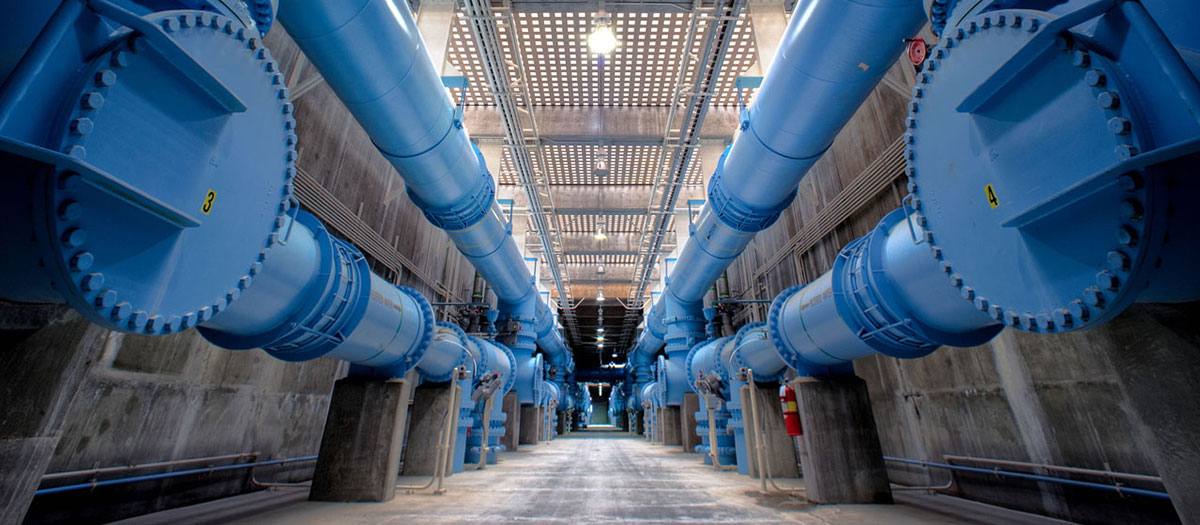 Blue transmission pipes run down the length of a hallway at the River Mountains Water Treatment Facility