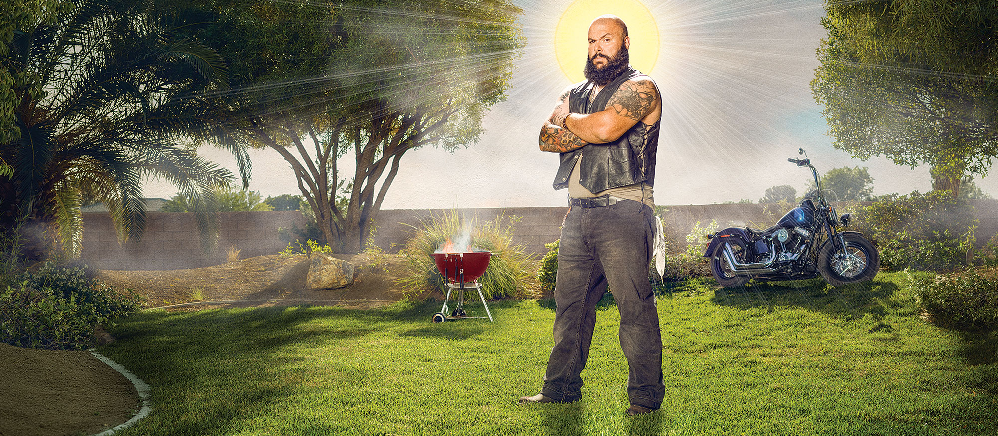 A biker stands on his lawn with a sun shining behind him, making him look like an angel