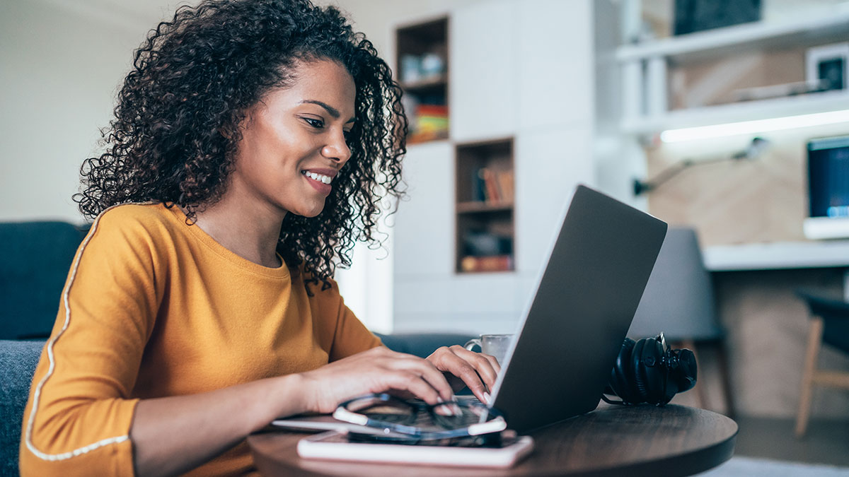 A black woman in a yellow top using a computer
